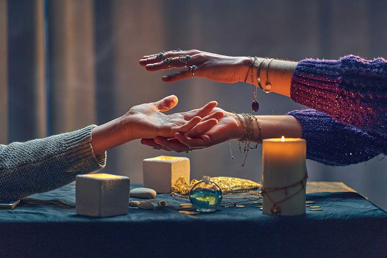 Psychic reader spelling over hand palm during occult spiritual rite and divination ritual around candles and other magical accessories