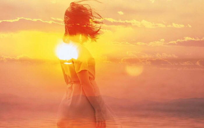 Double exposure of young woman and sunset sky