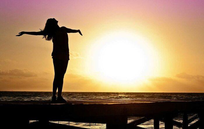 woman feeling happy at sunrise