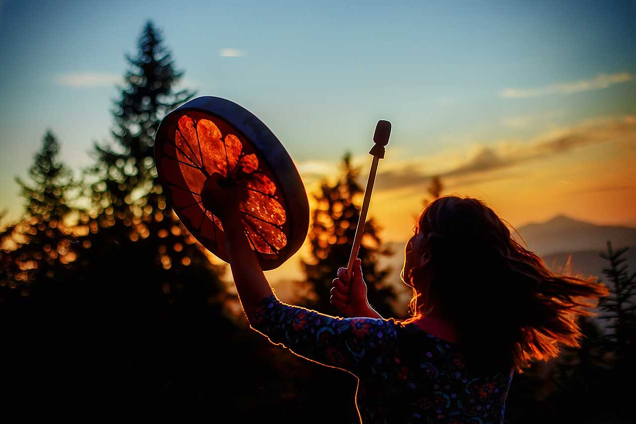 shamanic girl playing on shaman frame drum in the nature