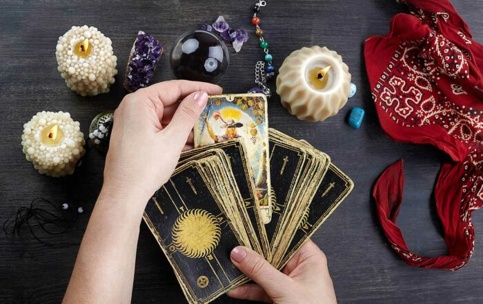 Fortune teller female hands and tarot cards on dark wooden table. Divination concept.