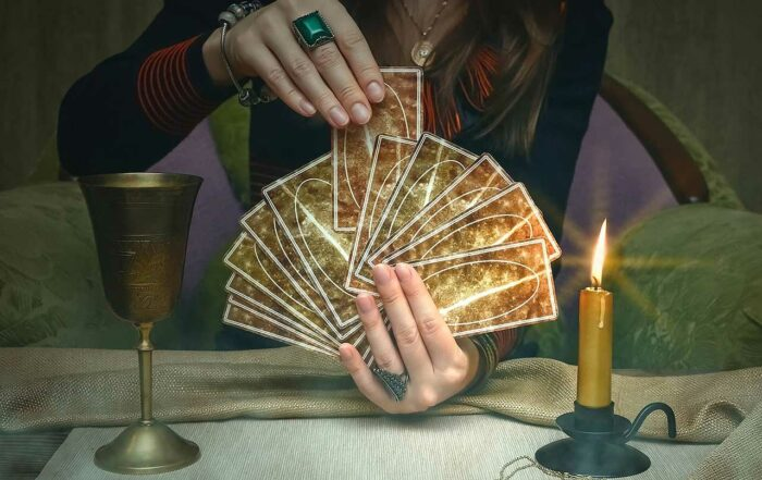 Woman fortune teller holding a deck of tarot cards.