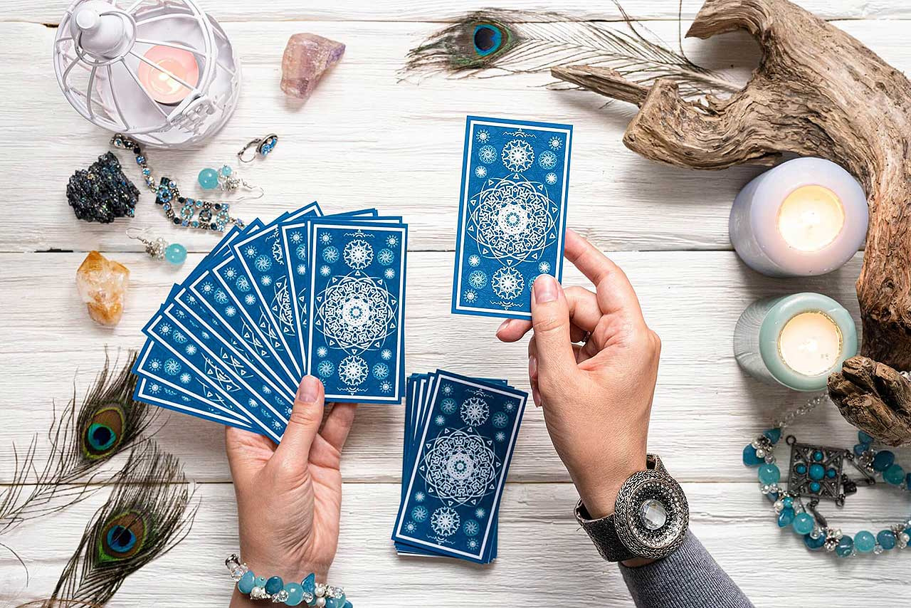 Fortune teller woman with blue tarot cards over white wooden table background.